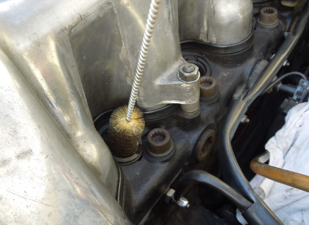 Cleaning fuel injector hole with brass brush